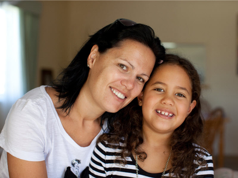 Mother and daughter smiling at the camera