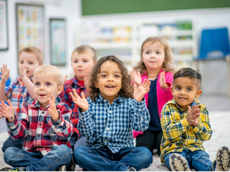 Happy kids sitting and clapping inside a school