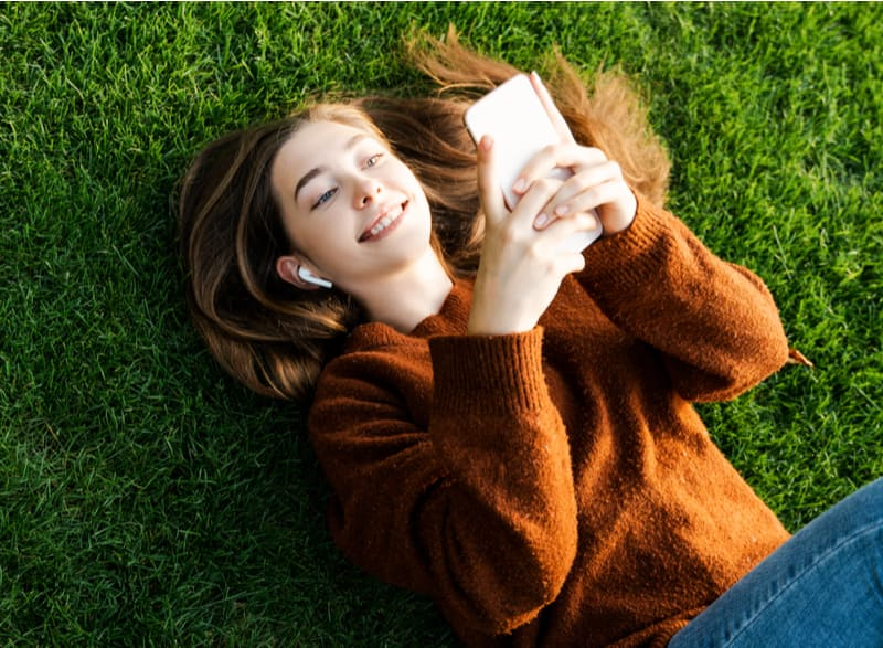 Smiling happy teenager girl looking at her smart cell phone