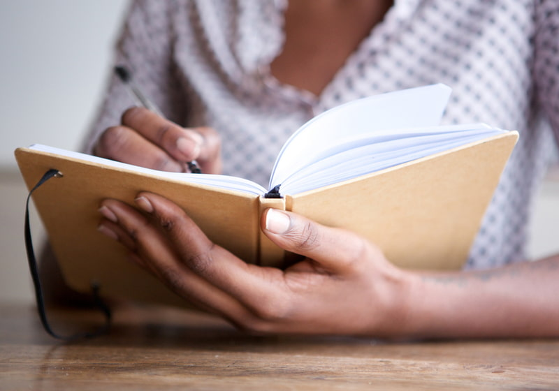 Female author at home writing in journal