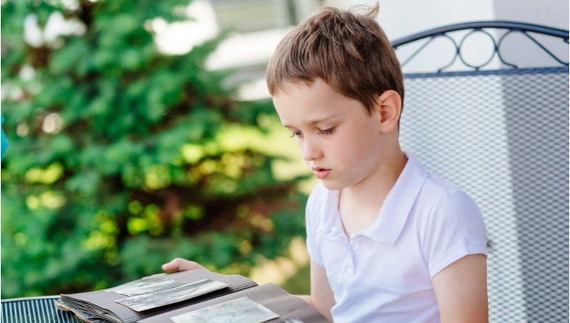 Little boy browsing old photo album